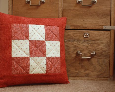 Red and cream patchwork quilted cushion by Mrs D